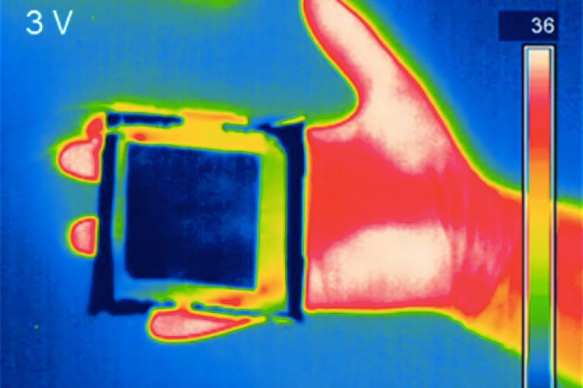 A piece of the material (blue square) masks the thermal signature of a human hand