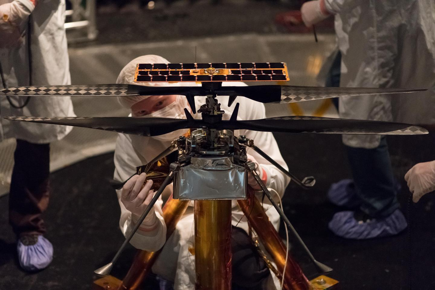 NASA engineers cover the main body of the Mars Helicopter in a protective thermal film
