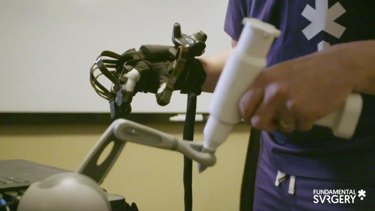 A HaptX Glove, along with a haptic feedback arm, is used with the Fundamental Surgery system