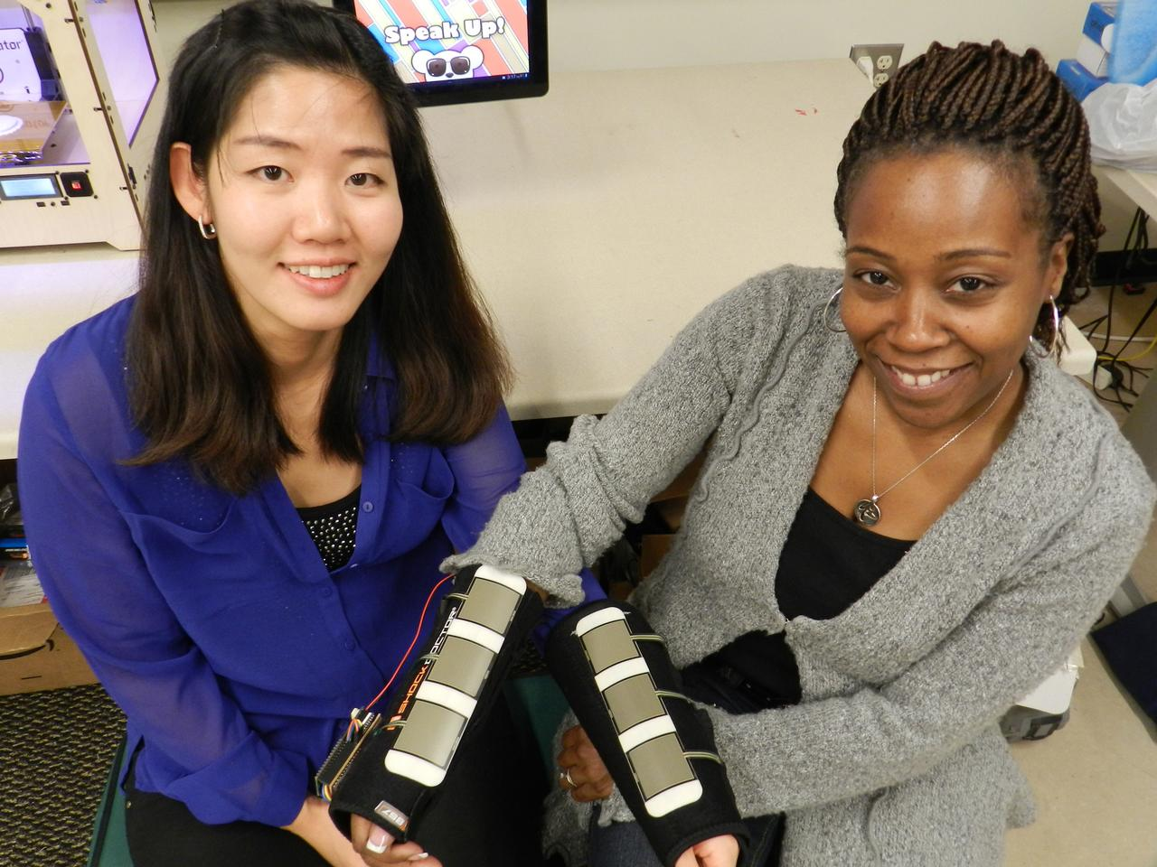 Ayanna Howard (right) and Hae Won Park (left) model the Access4Kids device that allows the motor impaired to control a tablet