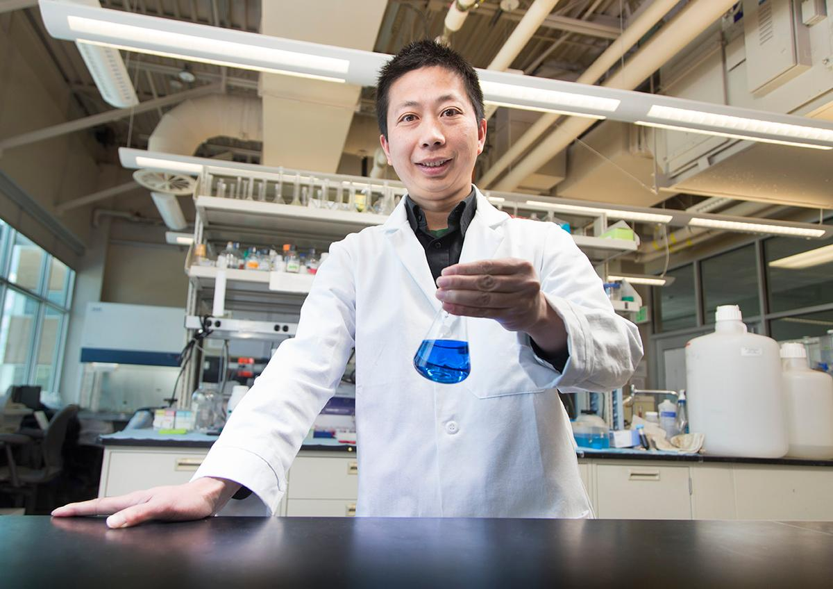 Lead scientist Dr. Jixun Zhan, with a flask of indigoidine