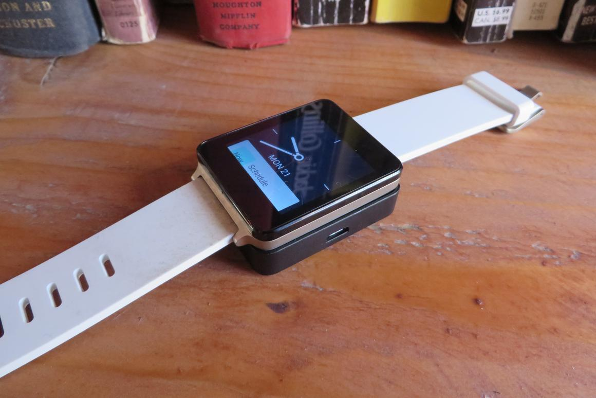 The G Watch atop its charging station, sans USB cord