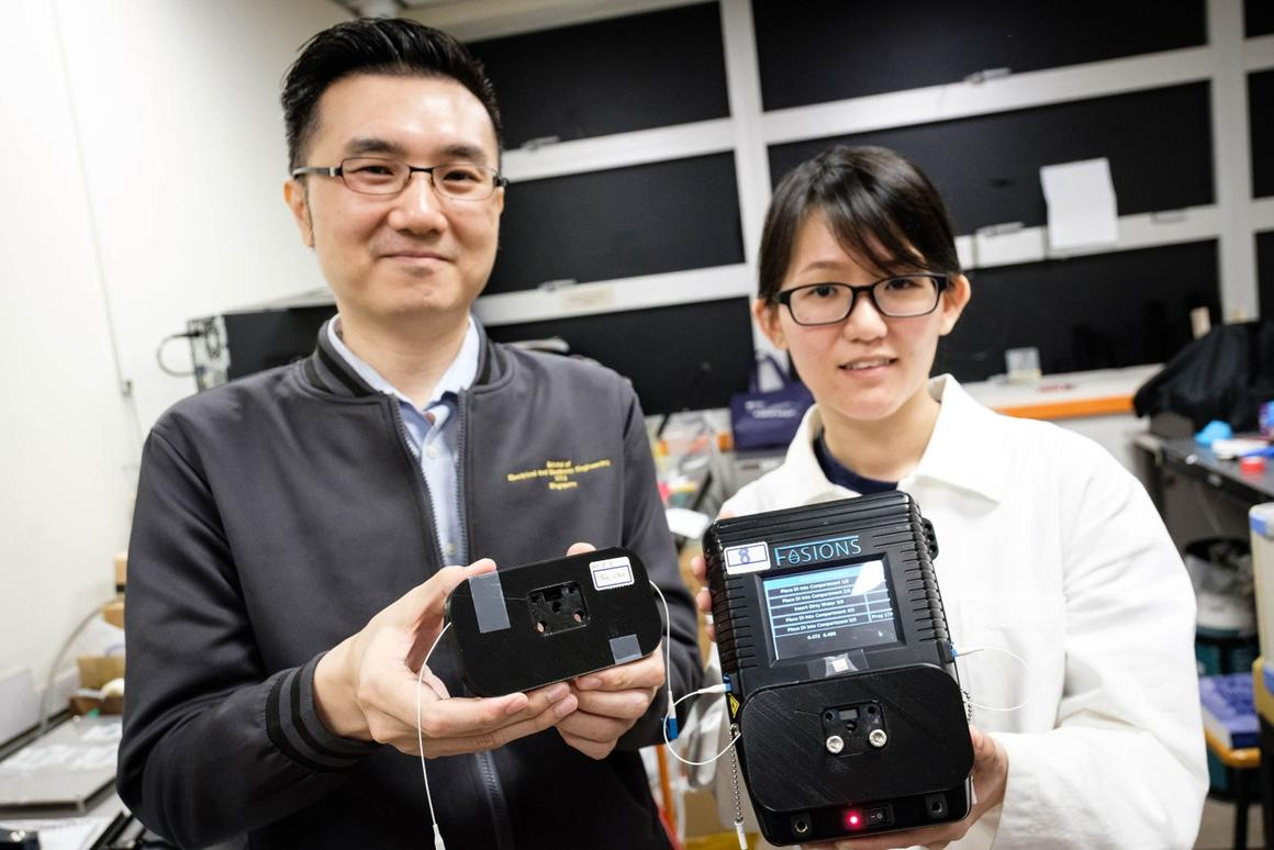 Assoc. Prof. Yong Ken-Tye (left) and PhD student Stephanie Yap, with the water-testing device