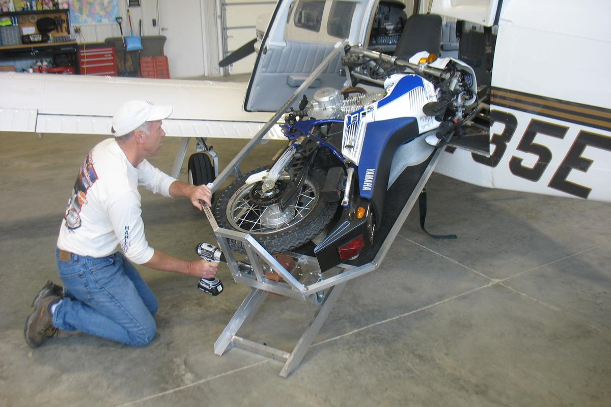 The MotoLOAD winches a MotoCYCLE into an airplane using a cordless drill
