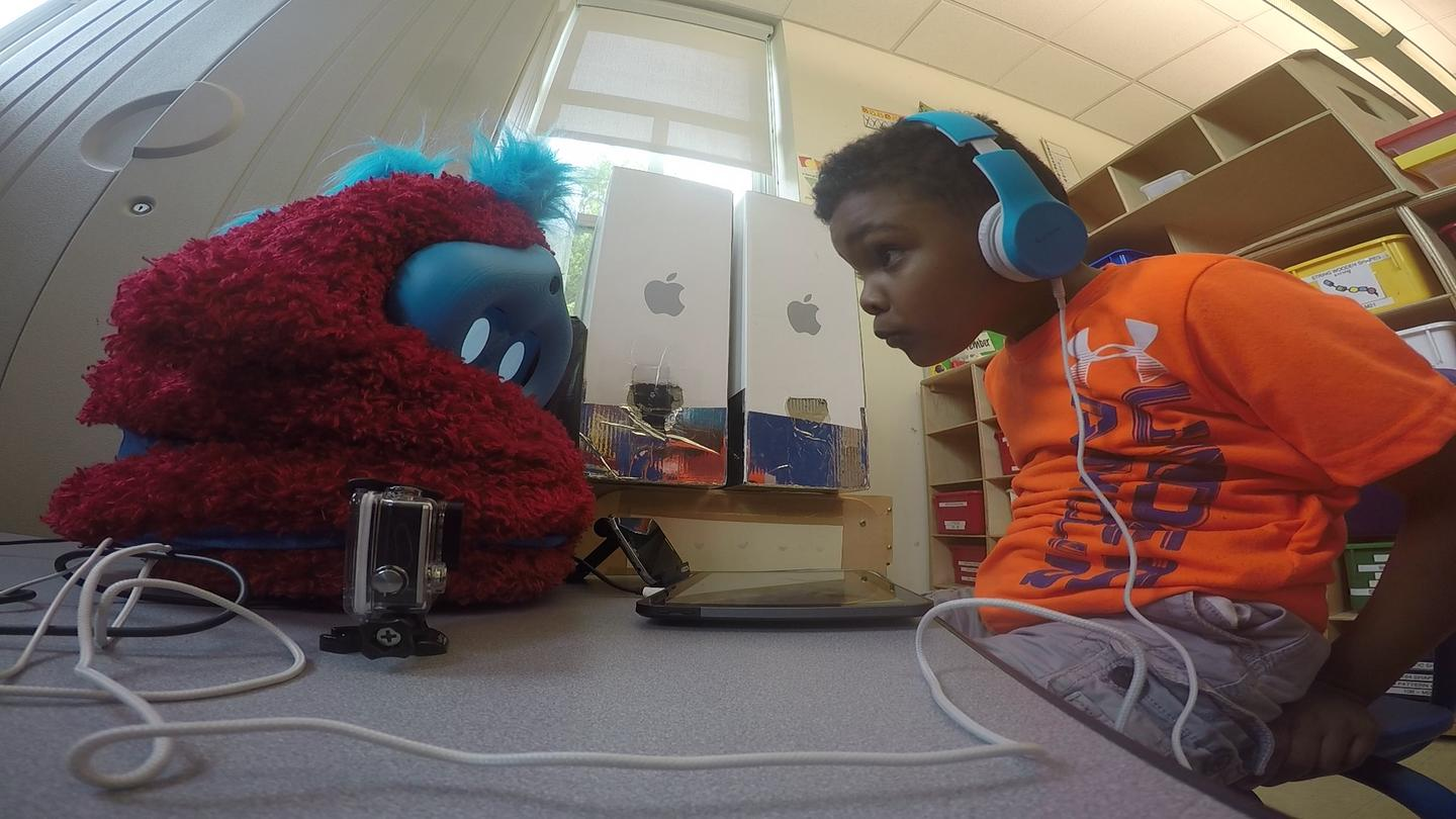 A child plays an interactive language learning game with Tega, a socially assistive robot