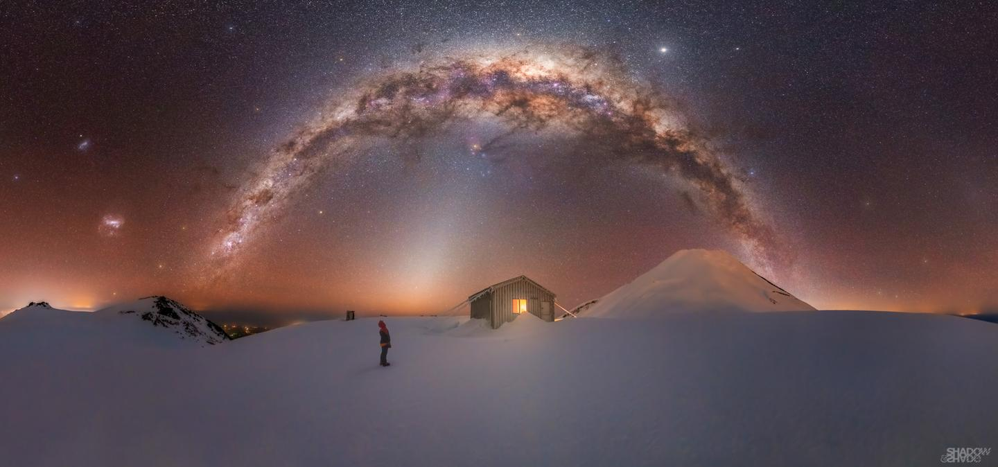 Mt. Taranaki Milky Way, shot on Fanthams Peak of Mt. Taranaki in New Zealand. The eerie image shows the Milky Way looming over a lonely cabin, at an elevation of 2,000 m (6,560 ft), while a lone hiker looks up in awe