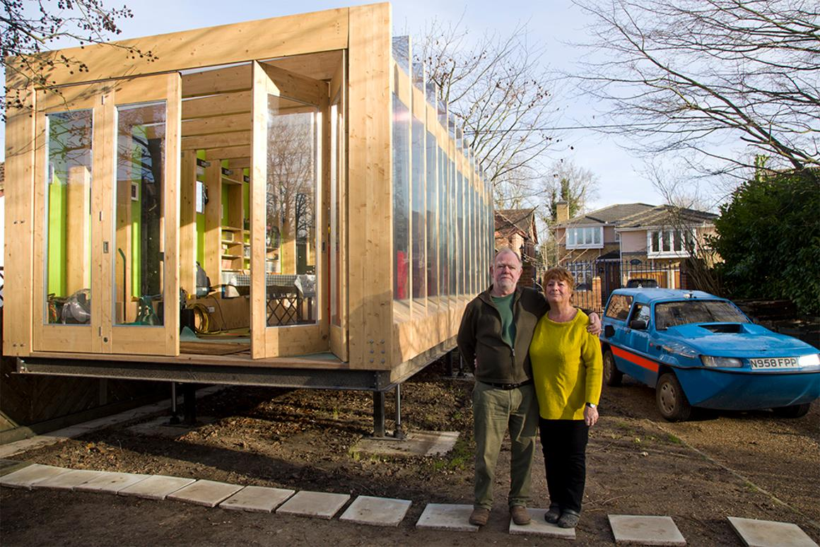 Erica and Peter in front of their flood-proof greenhouse and amphibious car