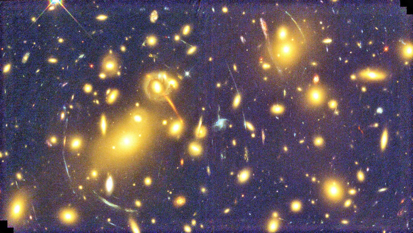 A view through massive galaxy cluster Abell 1689, showing the characteristic arcs of gravitational lensing
