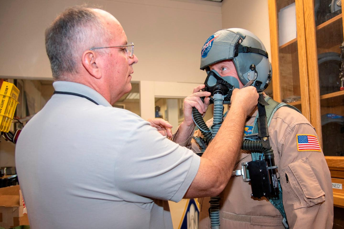 NASA pilot Jim Less is assisted by life support as he is fitted with a Cobham designed VigiLOX pilot oxygen monitoring system