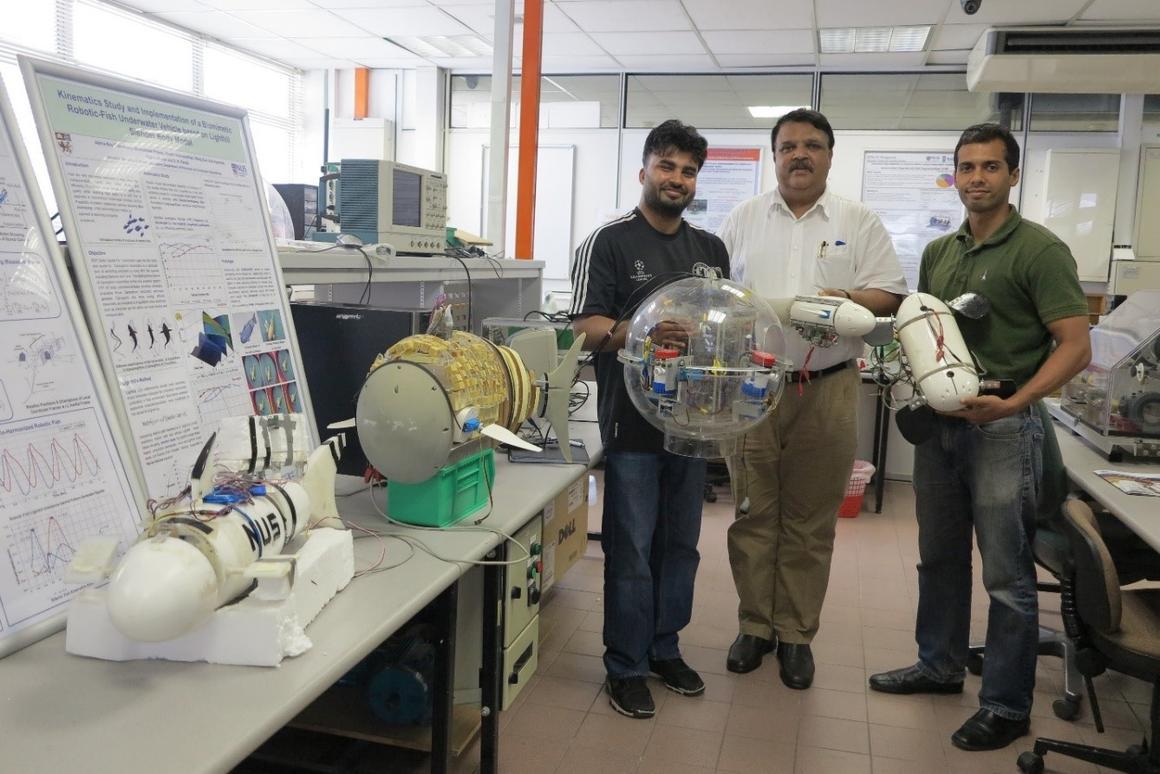 Bhuneshwar Prasad (left), Associate Professor S.K. Panda and Abhra Roy Chowdhury, holding the turtle robot at right (Photo: National University of Singapore)