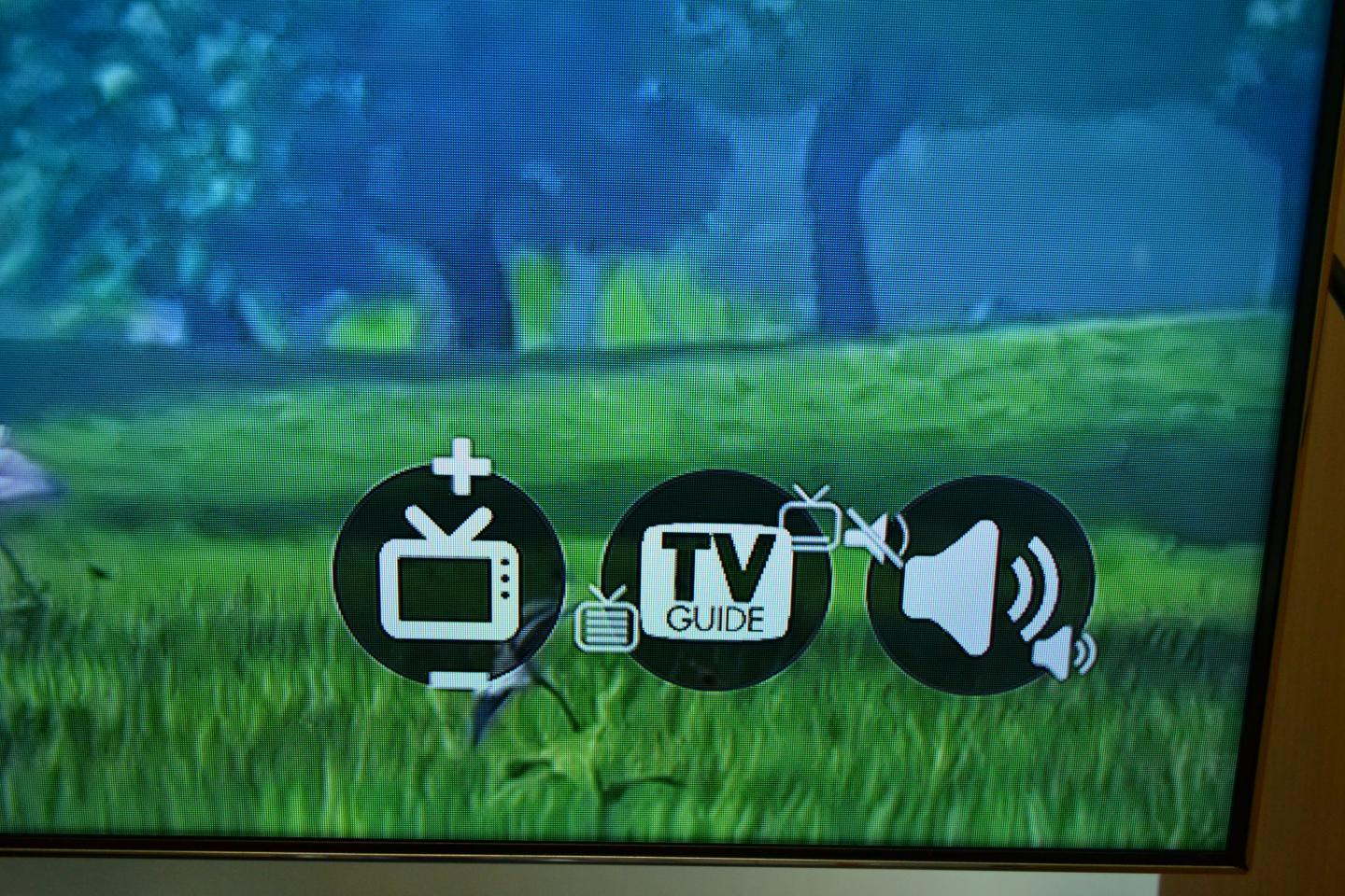 In one corner of the TV screen, there are a group of small circular widgets representing functions such as volume control or channel-changing