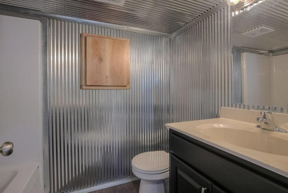 The container home'sbathroom features a shower and bathtub