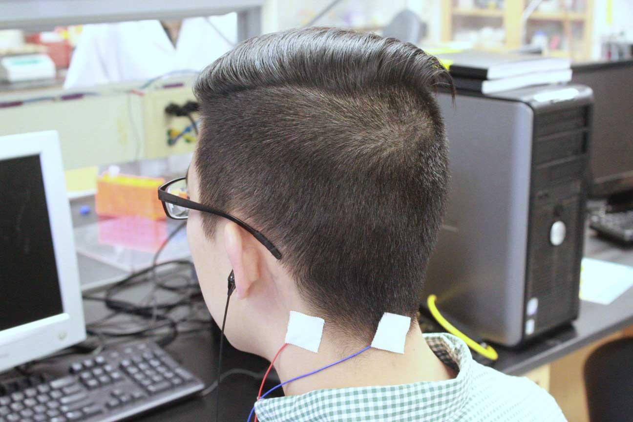 Chris Chang tests the tinnitus treatment device