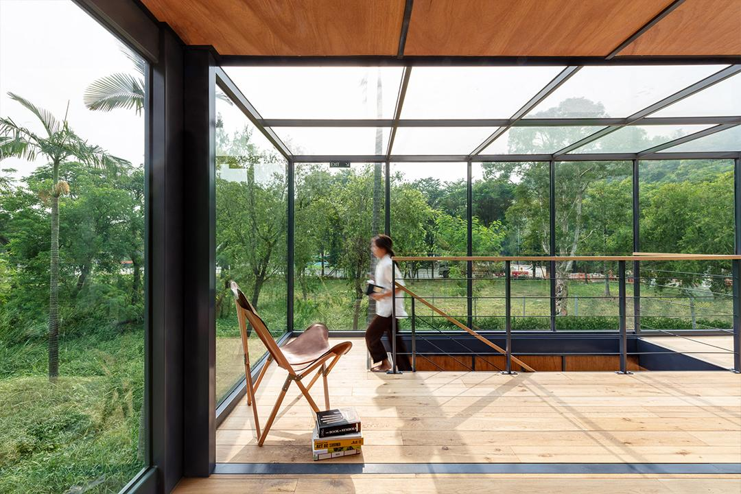 A fifth interior space is created by enclosing the fourth shipping containing with a large glass atrium