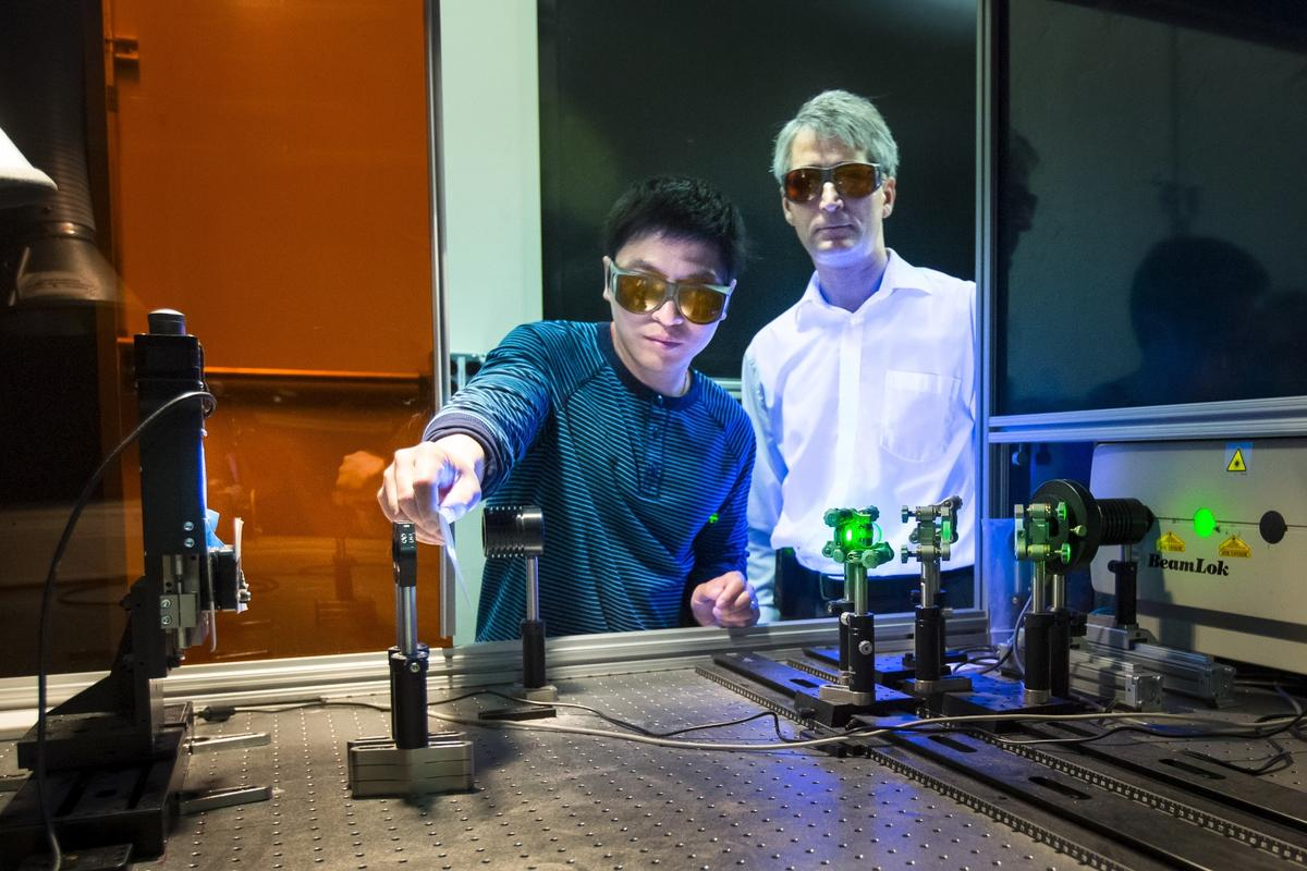 Jian Chen (left) and Adrian Sabau (right) work with a laser to prepare a carbon fiber composite surface for joining with aluminum