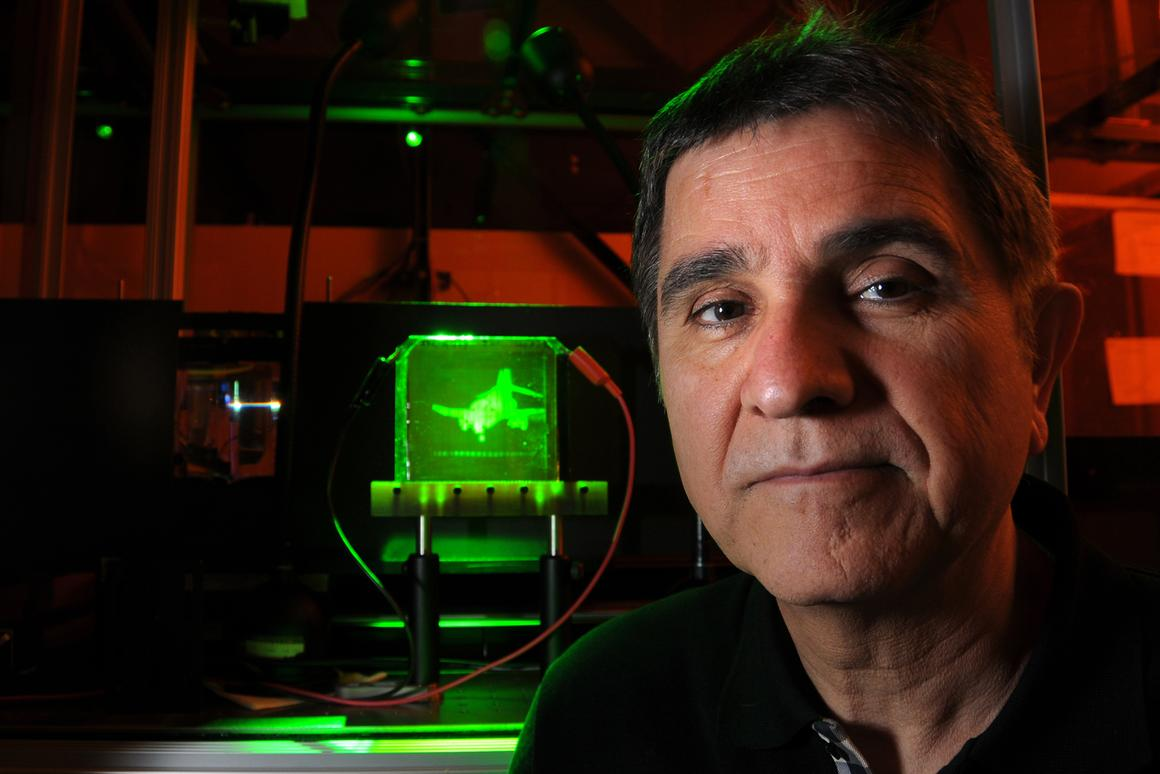 Project leader Nasser Peyghambarian with a refreshable, holographic image of an F-4 Phantom jet (Photo: University of Arizona)