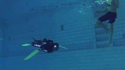 ETH Zurich's naro-tartaruga, a robotic sea turtle, propels itself underwater with its fins while a researcher observes nearby