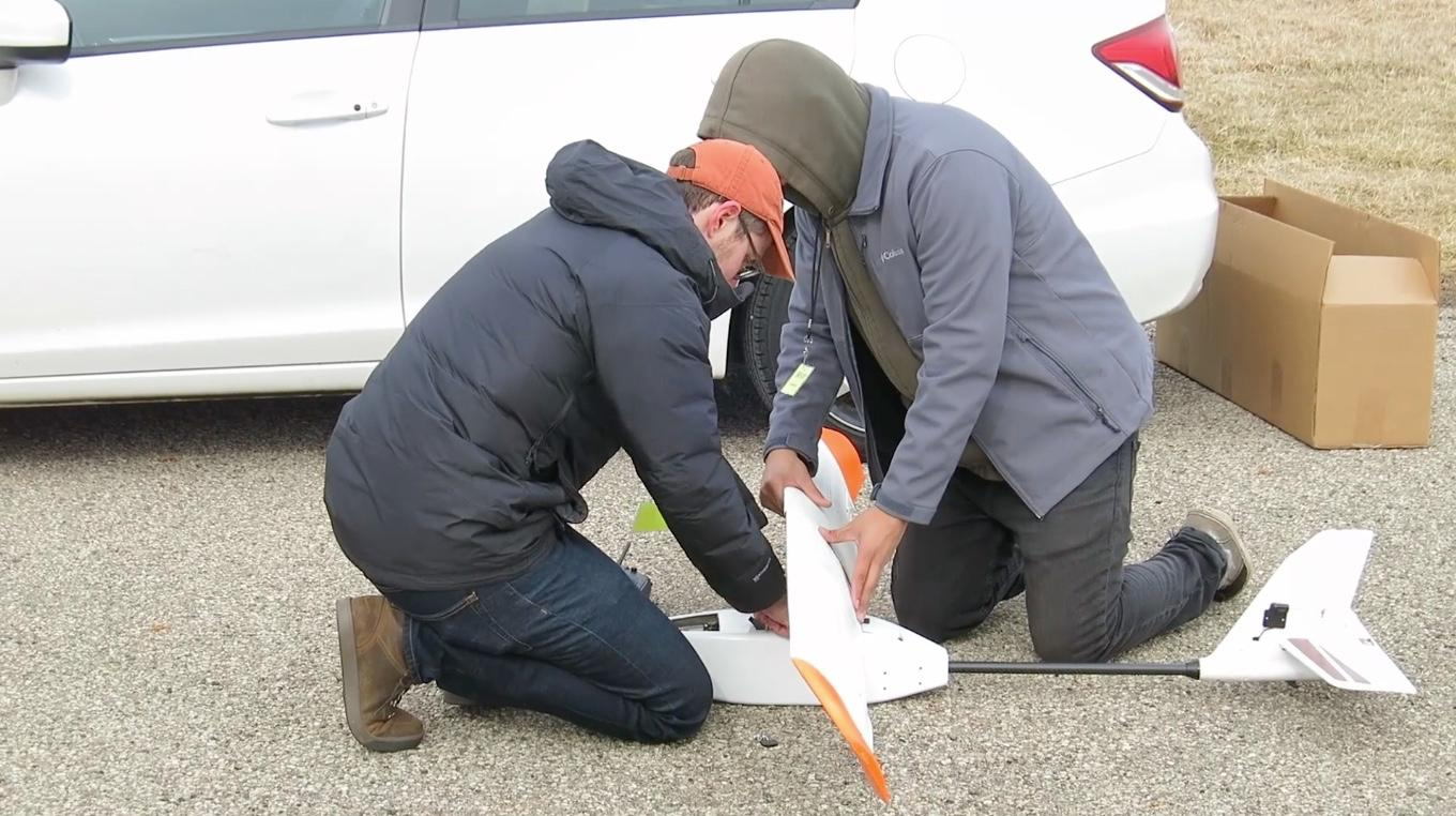 Research team members mount the battery wing on the drone