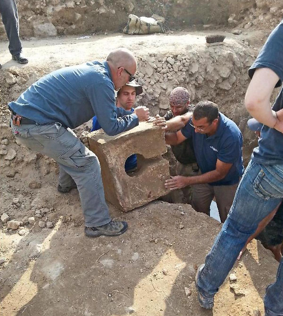 Archaeologists unearthing a stone toilet from a gate shrine at Tel Lachish, Israel
