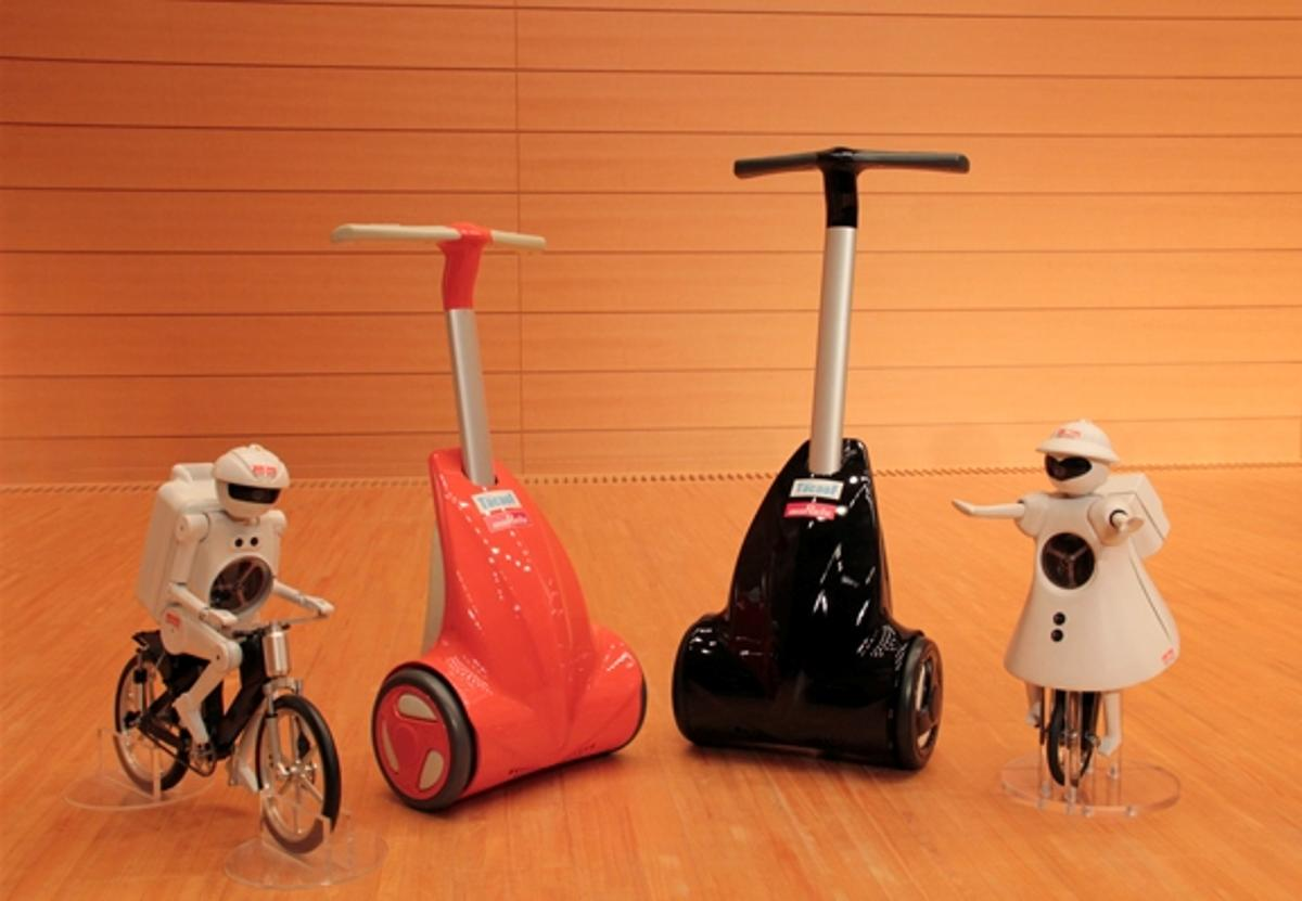 Murata Manufacturing's KeePace, a walk-assist device for the elderly or disabled, stands next to the company's mascot robots.