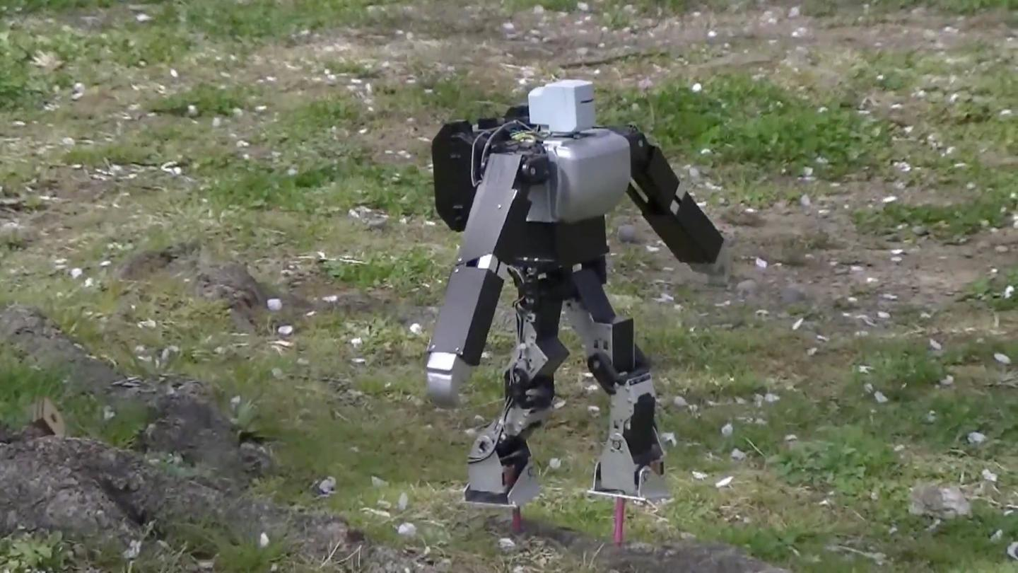 Dr. Guero's hobby robot kit balances on its stilts on the ground outside