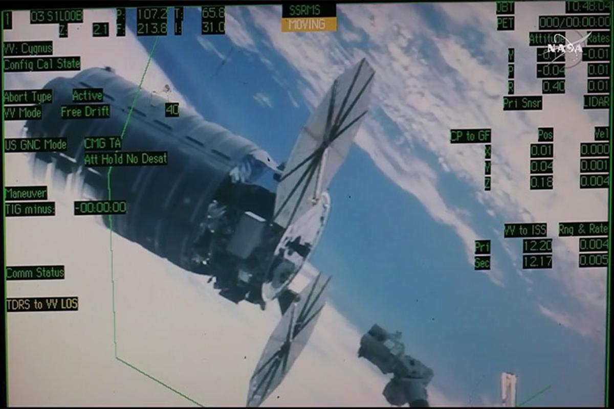 A computer overlay with engineering data provides video of the Canadarm2 robotic arm maneuvering to capture the Orbital ATK Cygnus space freighter