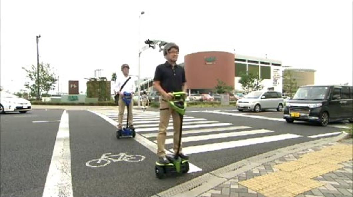Test subjects ride the Toyota Winglet personal mobility robot on public sidewalks and road crossings in Japan