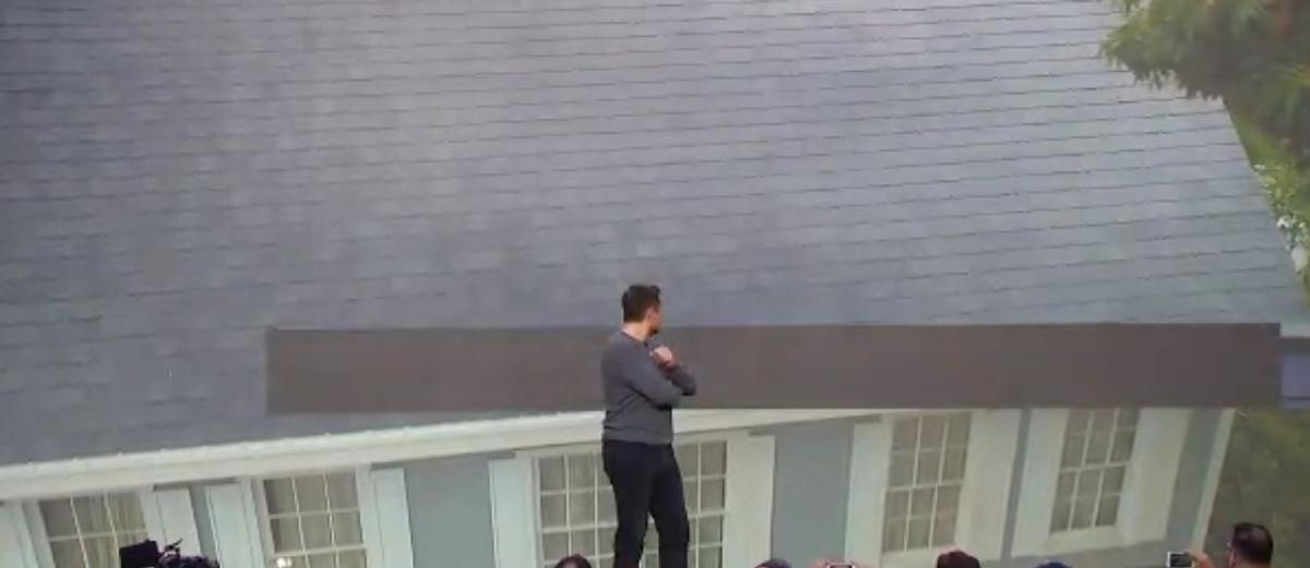 Tesla CEO Elon Musk admires his company's new solar roof tiles
