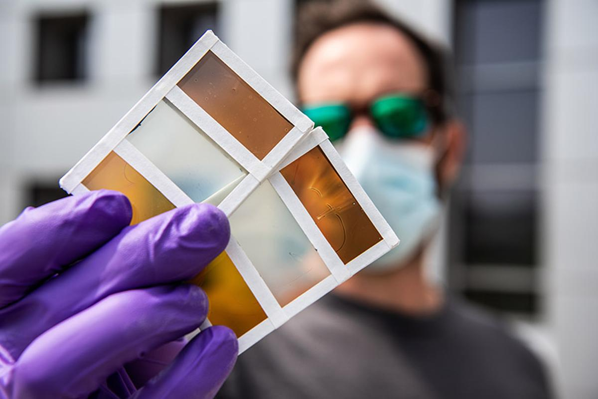 Researcher Lance Wheeler holds samples of the team's new thermochromic photovoltaic windows, which can switch colors in response to heat and generate electricity from sunlight