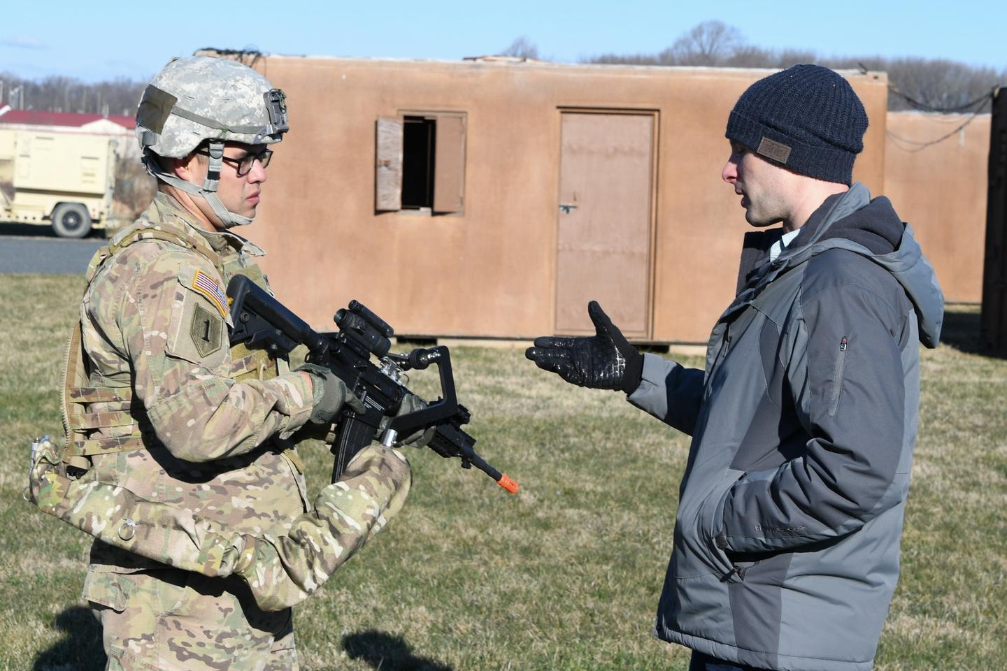 Army researcher Dan Baechle (right) briefs Sgt. Michael Zamora on how to use the Third Arm exoskeleton device