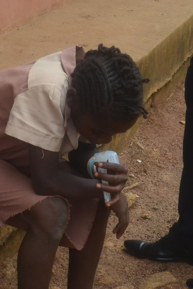 A primary school student spitting into a tube as part of the early saliva-test trials in Cameroon