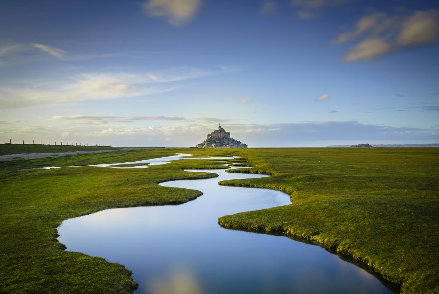 "Overall Winner - Mont Saint-Michel. ""Les Méandres: The medieval island commune of Le Mont Saint-Michel sits off the northwestern coast near the border between Brittany and Normandy in France.  This photograph, taken during the spring tide in early March 2018, shows the curious land formations known locally as Les Méandres. The channels fill up in late afternoon and reflect the setting sun to create a mirror pool effect."""
