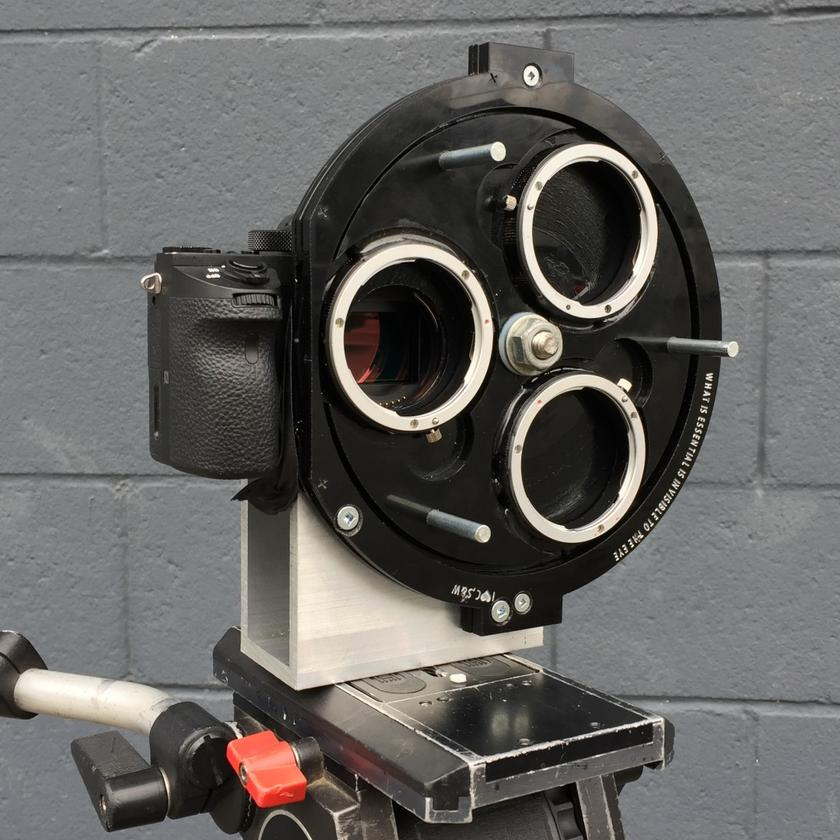 The prototype MultiTurret is attached to the camera via the body lens mount and an extra bracket, with a couple of bolts supporting system weight