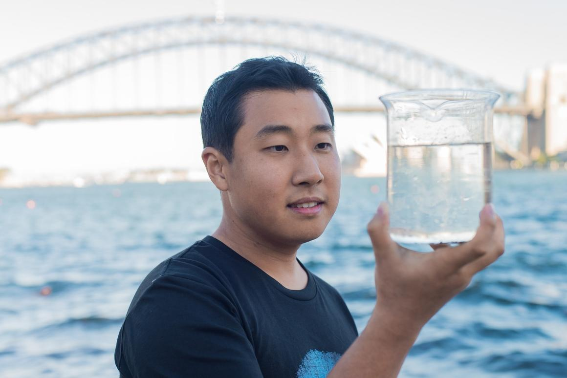 Dong Han Seo, of the CSIRO, holds a flask of water takenfrom Sydney Harbour, which has been purified to a drinkable standard thanks to a graphene-based filter