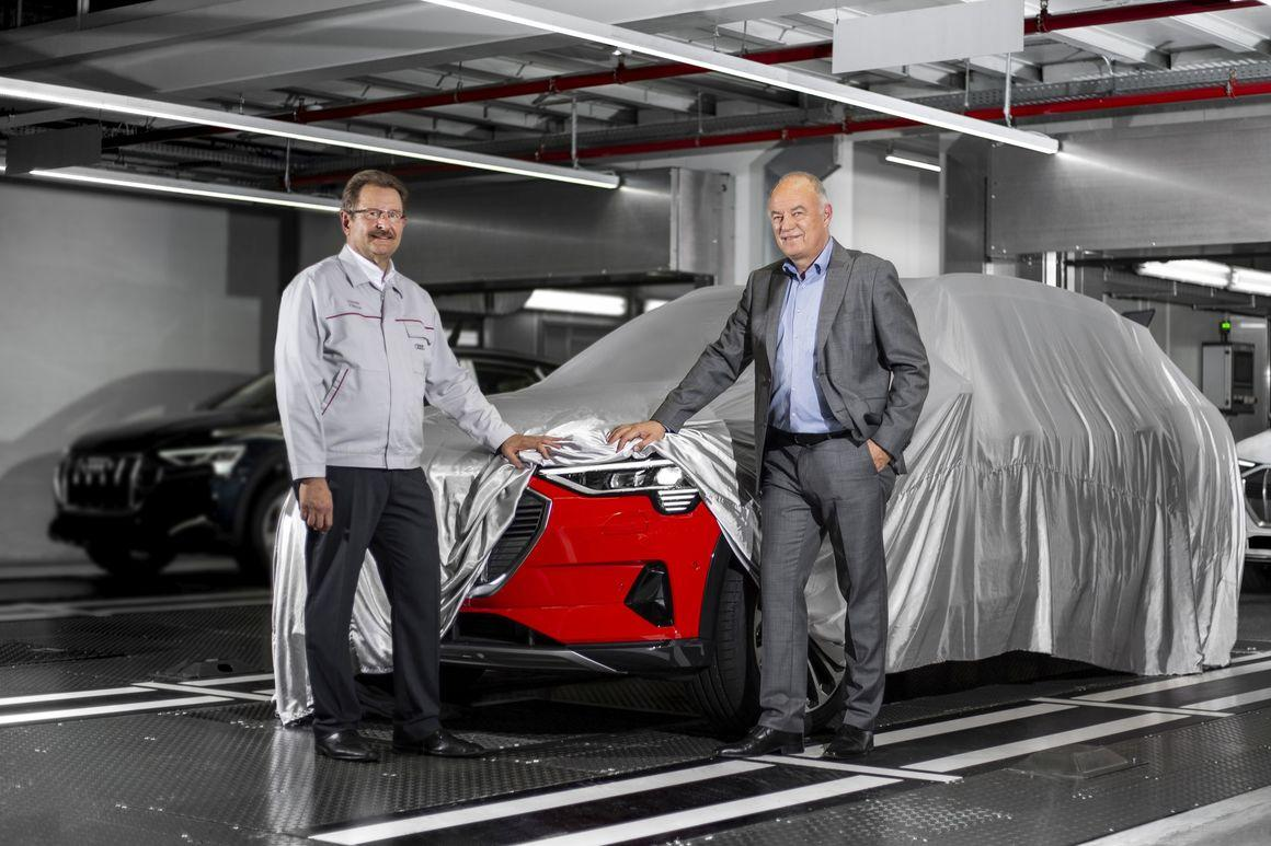 Patrick Danau (L), Managing Director of Audi Brussels, and Peter Kössler (R), Board of Management Member for Production and Logistics at AUDI AGand Chairman of the Board of Directors of Audi Brussels, takea peek at the first Audie-tronmodels from series production