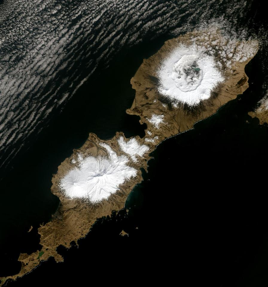 The 10-km wide caldera which formed as a result of the Okmok eruption in 43 BCE can be seen in the upper snowy region of this image