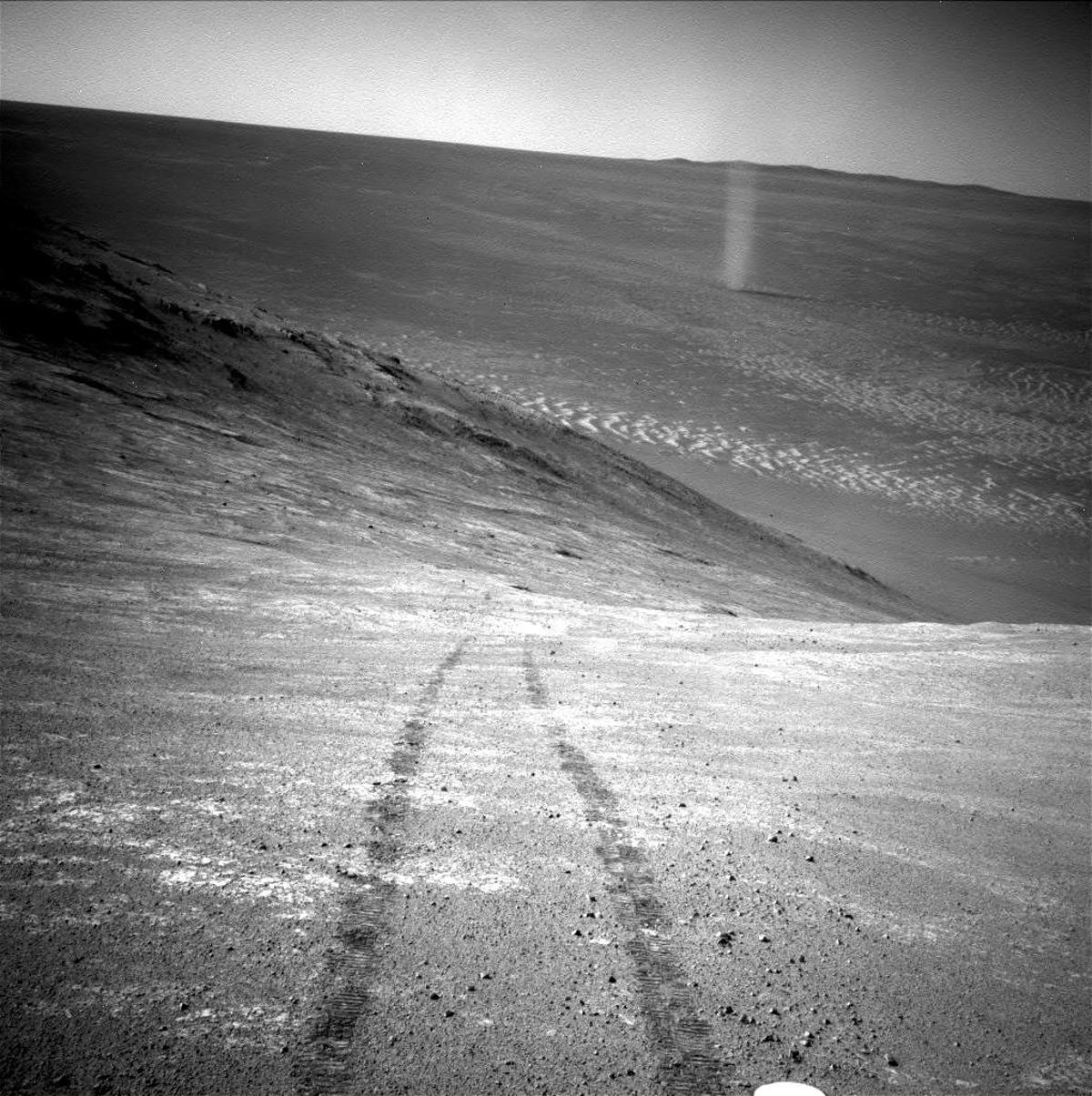 Opportunity's track prints are apparent in the lower image, while the dust devil cuts a ghostly figure in the top right of the shot