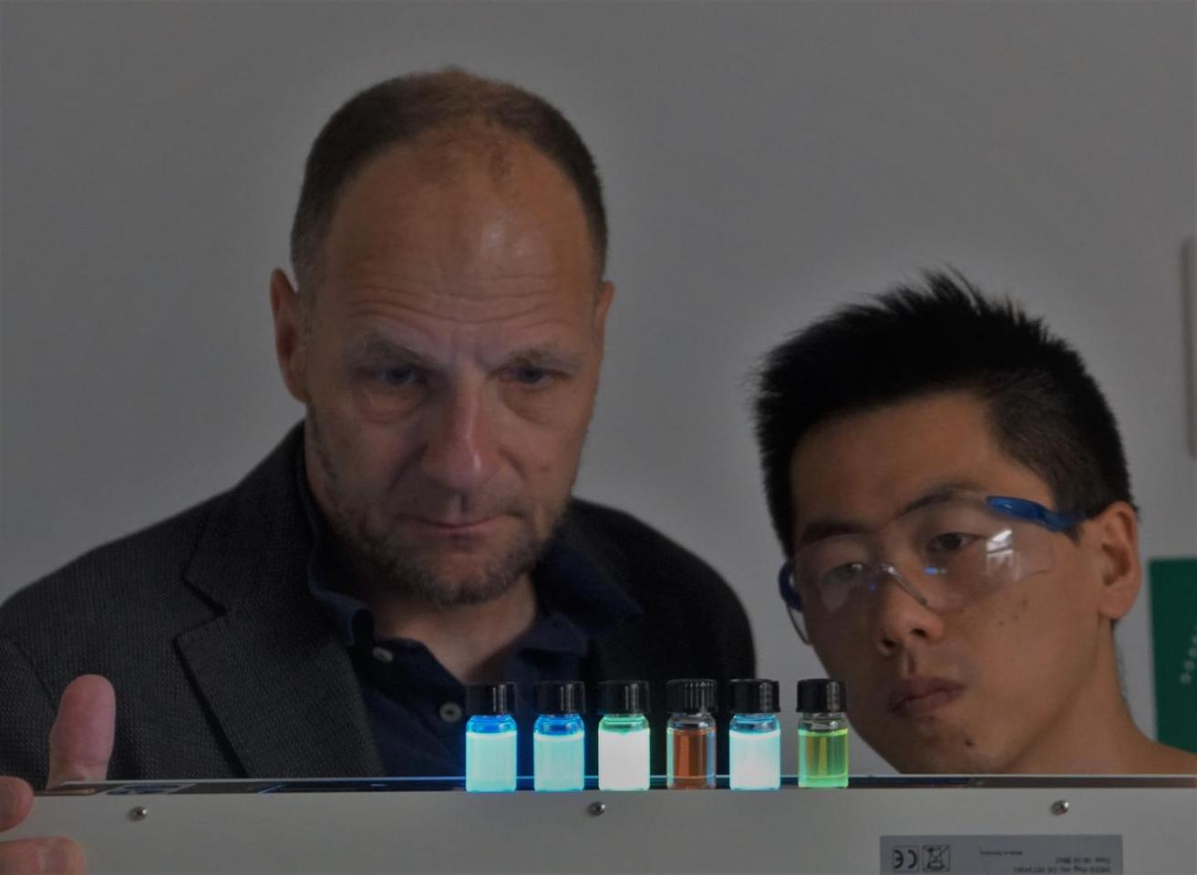Prof. Uwe Bunz (left) and doctoral student Jinsong Han, with a selection of glowing polymer dyes
