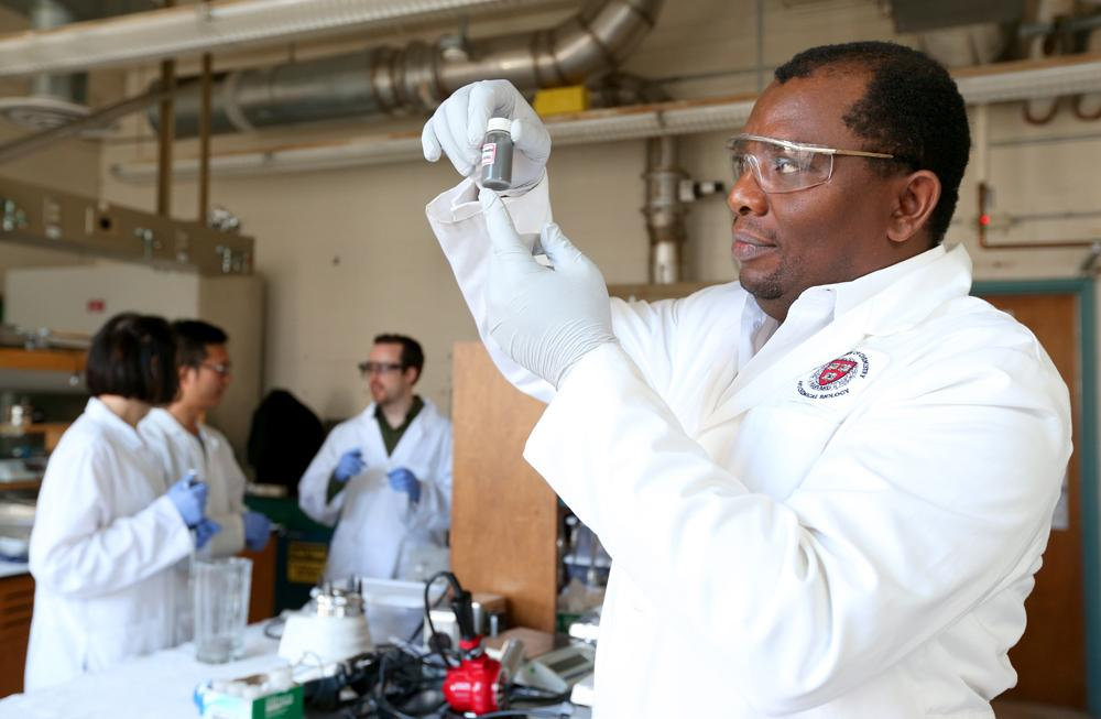Assistant professor Martin Thuo holds up a vial of the liquid-metal particles he and his group created – behind him are, left to right, Simge Cinar, Jiahao Chen and Ian Tevis