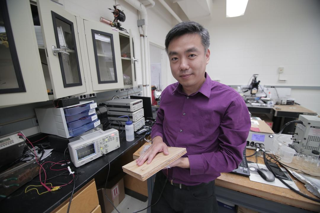 Xudong Wang, from UW-Madison, with a prototype section of the energy-harvesting flooring