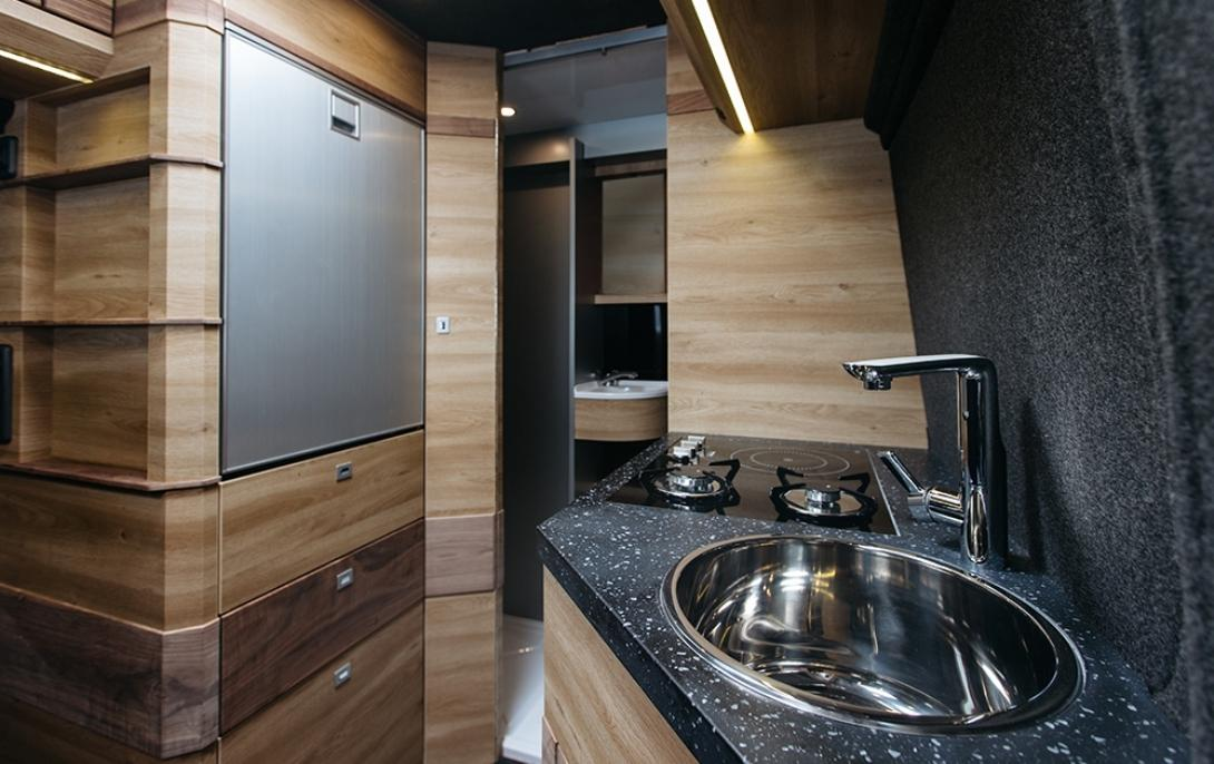 The kitchen area spans across the aisle and includes an oven/broiler, three-burner cooktop, sink and fridge/freezer