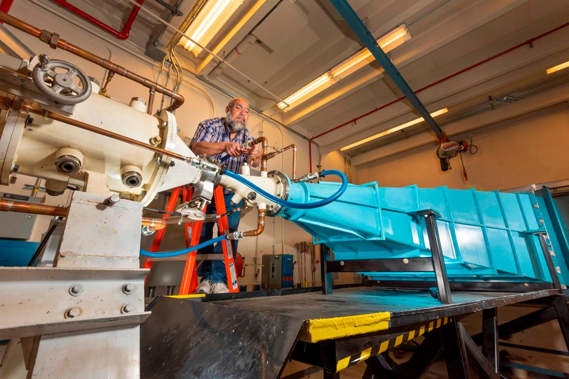 Sandia National Laboratories researcher Leonard Martinez connects a high-voltage-insulating line that circulates oil between a coaxial transmission line (white tube on the left) and the blue oil-filled transmission horn. of the EMES machine