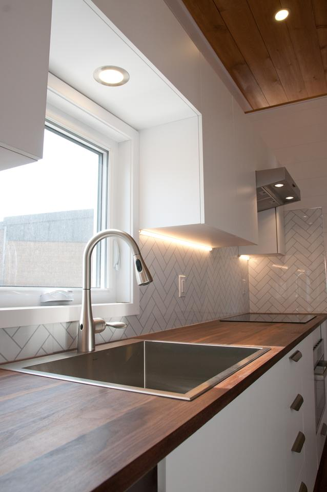 The Ébène V4's kitchen features a large stainless steel sink with a motion-activated faucet