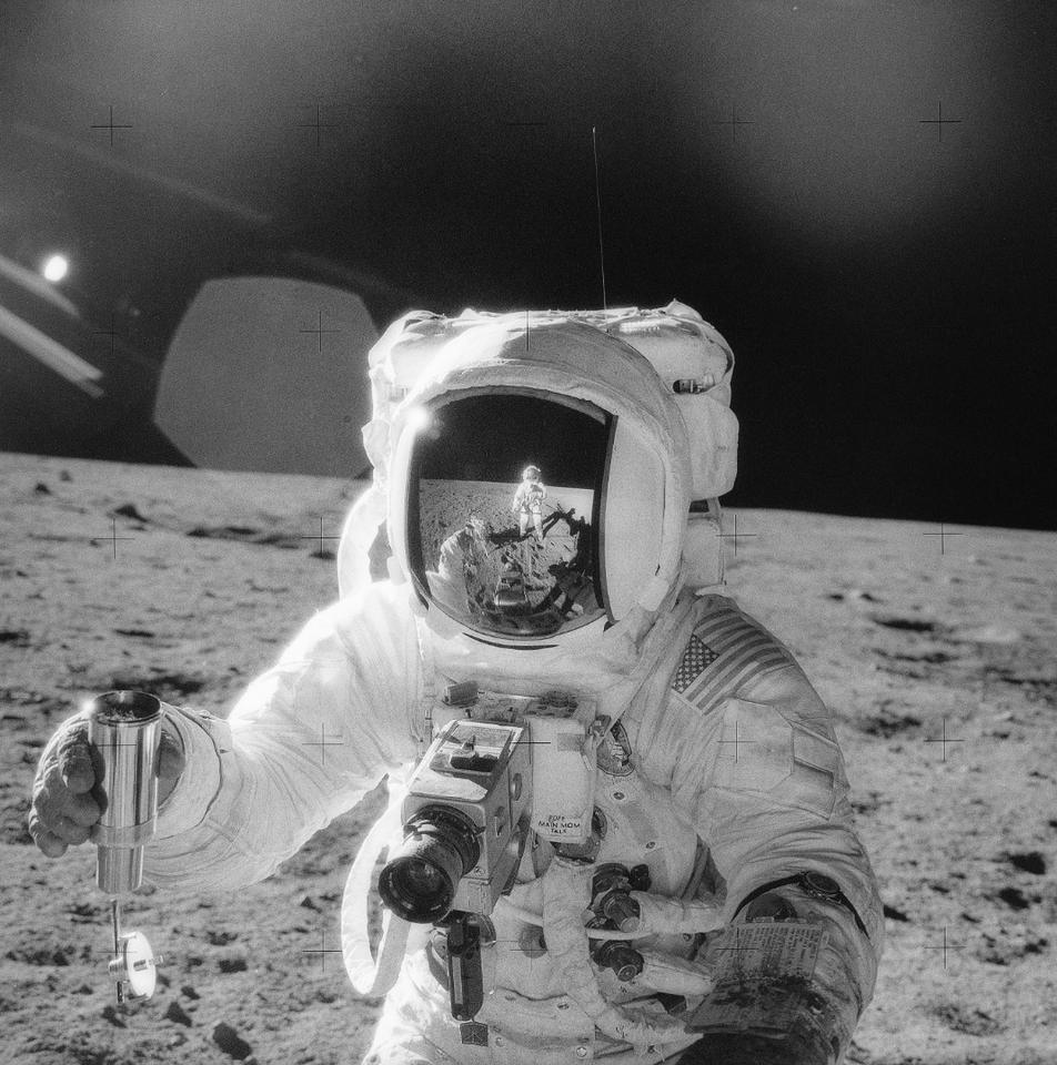 A NASA astronaut holds a container of lunar soil on the Moon's surface in 1969