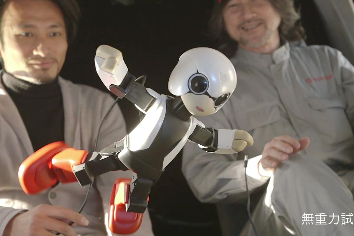 Kibo the Japanese communication robot floats in zero gravity aboard an airplane with its creator, Tomotaka Takahashi (left background)