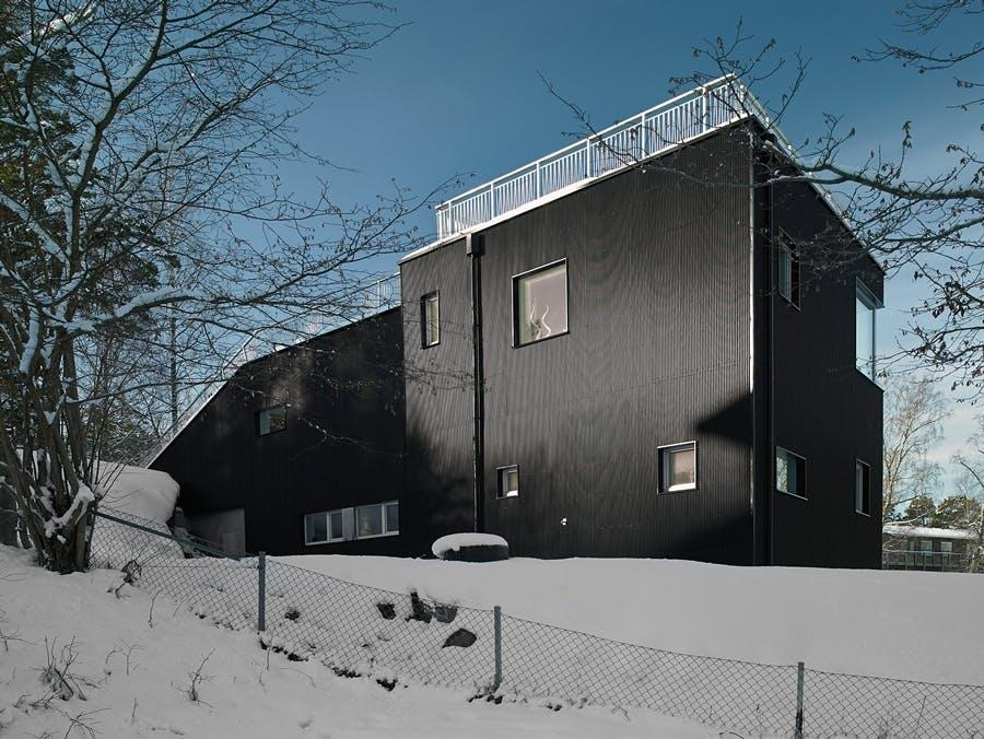 The Pulkabacken home by Street Monkey Architects in Värmdö, Sweden, featuring a large, grass-covered ground-to-roof slope that provides privacy and can be used for sledding in the snow