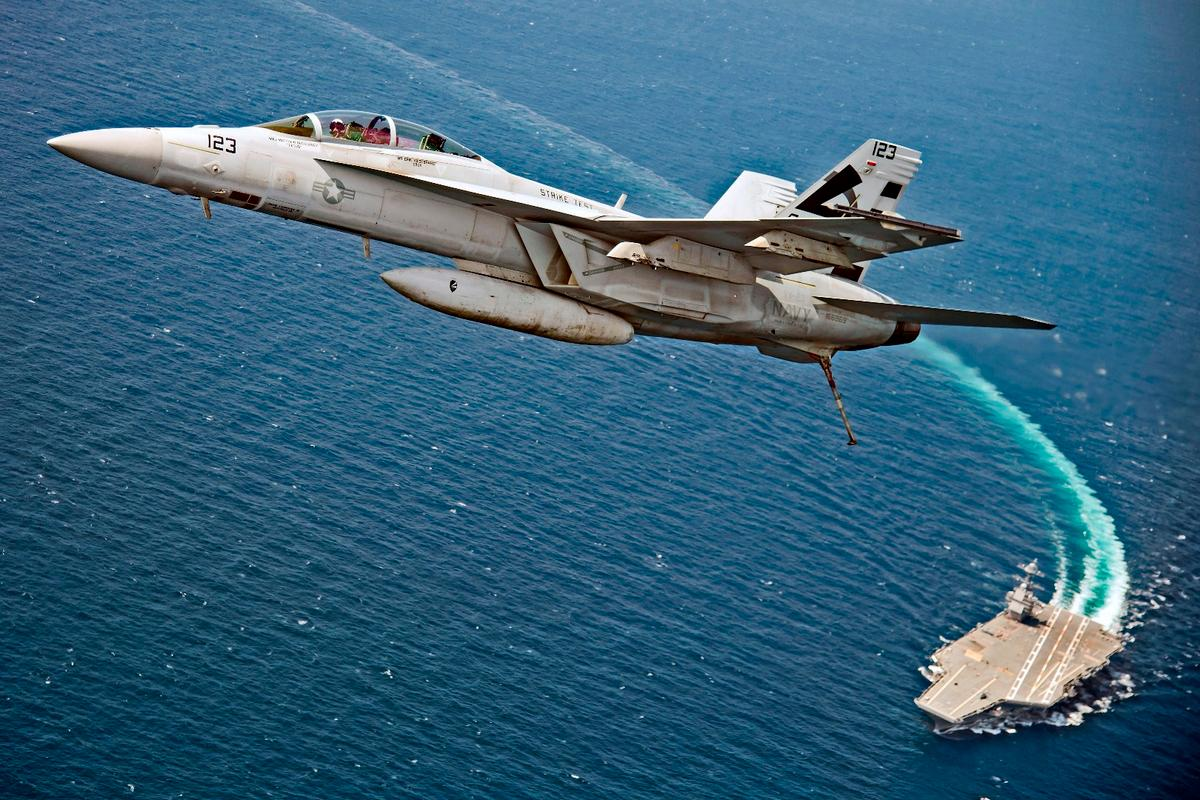 An F/A-18F Super Hornet assigned to Air Test and Evaluation Squadron (VX) 23 flies over USS Gerald R. Ford (CVN 78)