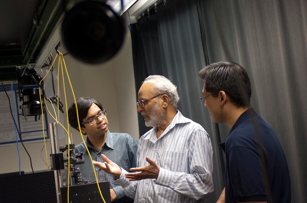 Spectroscopy Lab graduate students Ishan Barman, left, and Chae-Ryon Kong, right, talk with lab Associate Director Ramachandra Rao Dasari, center (Image: Patrick Gillooly)