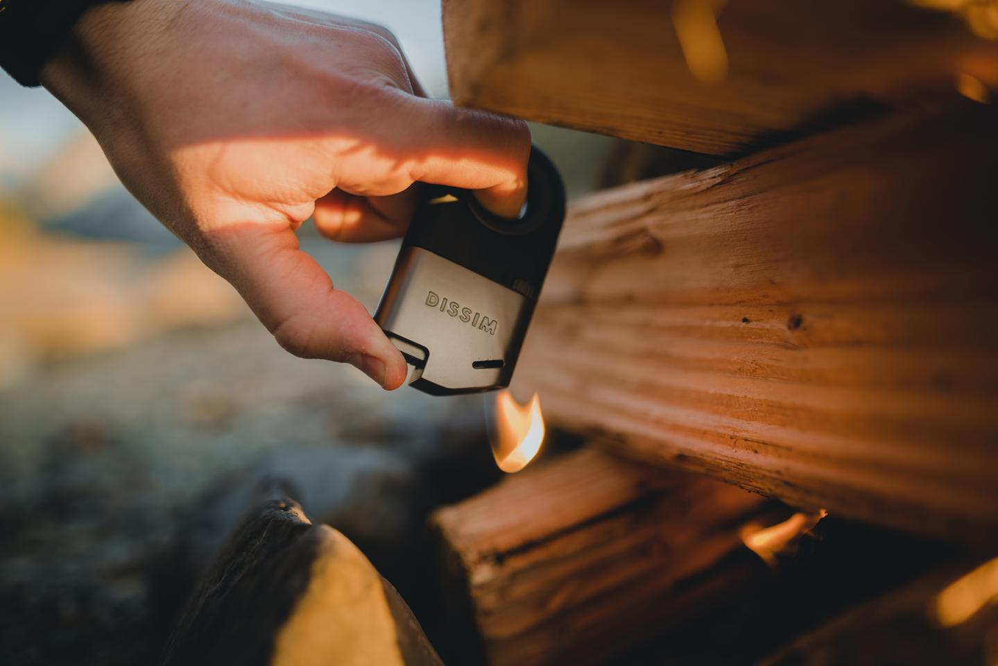Lighting a tinder/kindling/fuel stack is a situation in which a small disposable lighter is almost guaranteed to burn your thumb; the Dissim lighter makes it less precarious