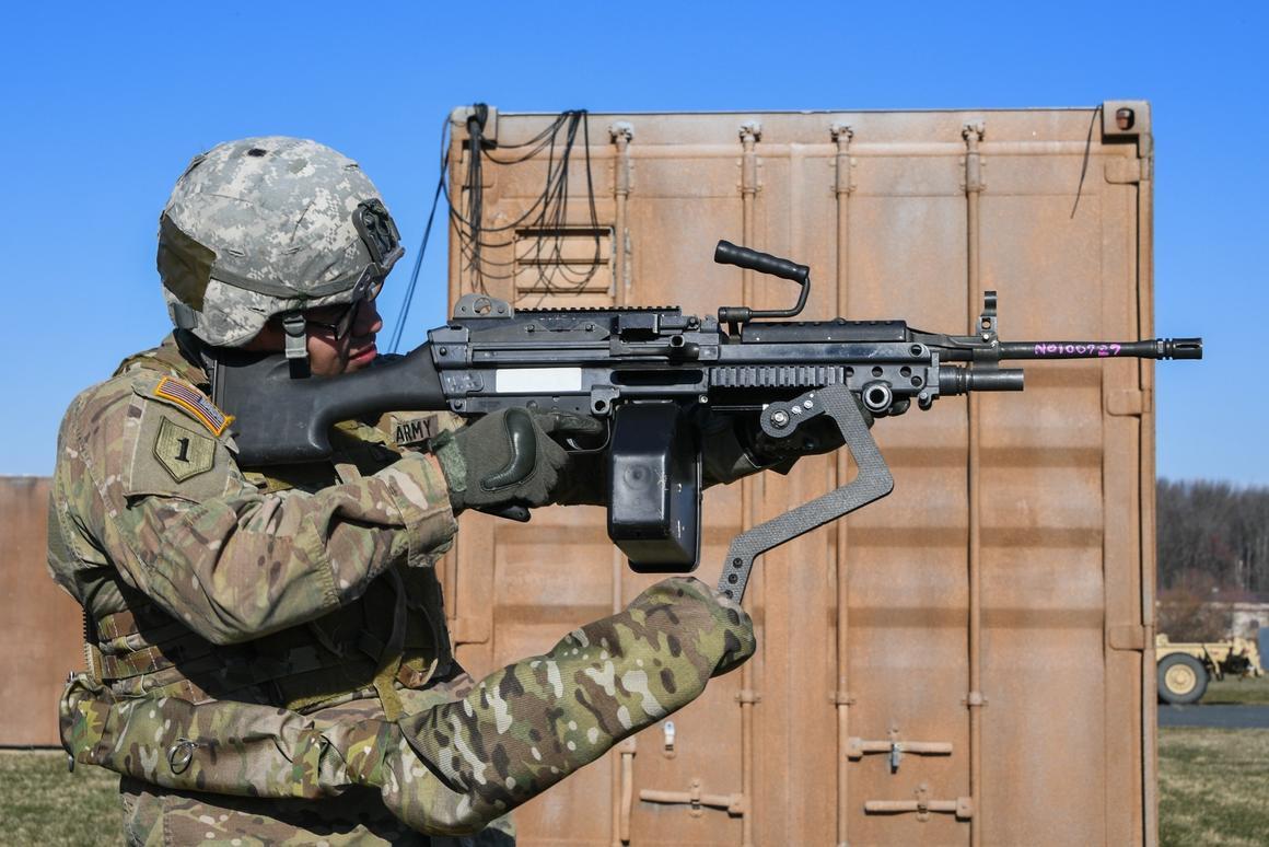 Army Sgt. Michael Zamora uses a prototype Third Arm exoskeleton toaim an 18-lb M249 light machine gun